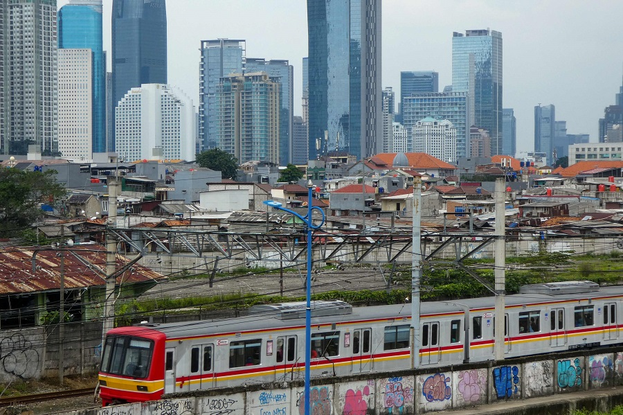 A commuter train is seen against the skyline of downtown Jakarta, Indonesia, on 14 April 2020. (Bay Ismoyo/AFP)