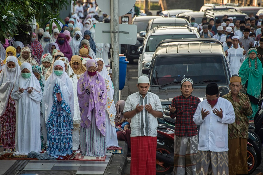 Indonesians attend Eid al-Fitr prayers, marking the end of the Muslim holy month of Ramadan, on a street in Surabaya on 24 May 2020. (Juni Kriswanto/AFP)