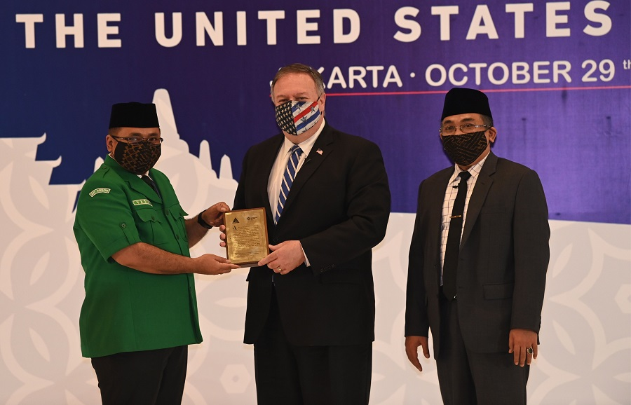 US Secretary of State Michael Pompeo (centre) receives a placard from Yakut Qoumas (left) General Chairman of Gerakan Pemuda Ansor next to Yahya Cholil Staquf (right) General Secretary of Nahdlatul Ulama at the Nahdlatul Ulama in Jakarta on 29 October 2020. (Adek Berry/Pool/AFP)
