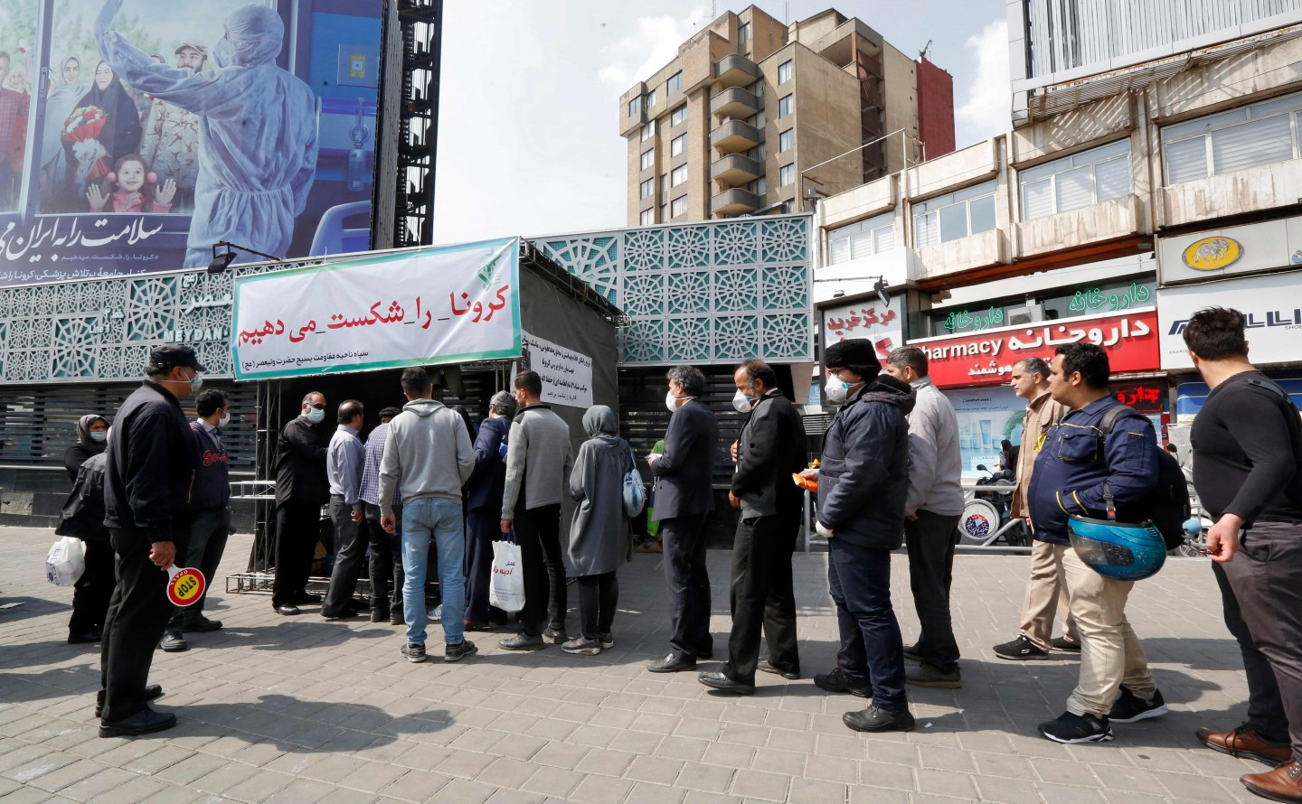 People queue in line to receive packages for precautions against the Covid-19 coronavirus provided by the Basij, a militia loyal to Iran's Islamic republic establishment, from a booth outside Meydan-e Vali Asr metro station in the capital Tehran on 15 March 2020. (STRINGER/AFP)