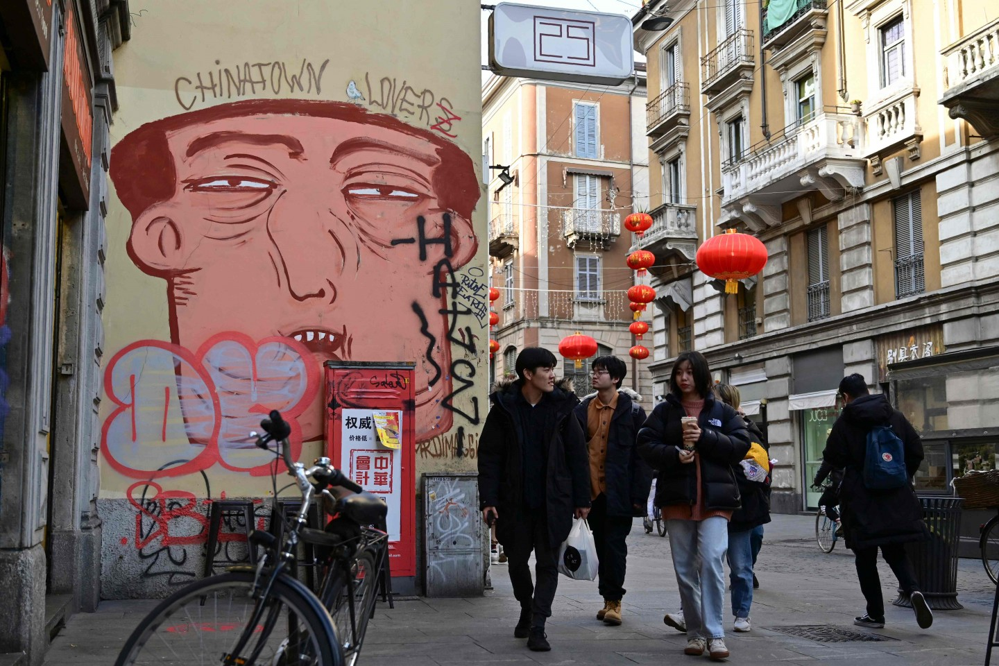 People pass by a mural depicting a chinese face in Via Paolo Sarpi, the commercial street of the chinese district of Milan on 30 January 2020. (Miguel Medina/AFP)