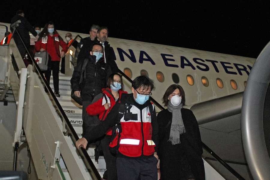 This photo provided by Italian news agency Ansa on 13 March 2020 shows Chinese medics going down a China Eastern flight after landing at Rome's Fiumicino international airport from Shanghai, bringing medical aid to help fight the new coronavirus in Italy. (STRINGER/ANSA/AFP)