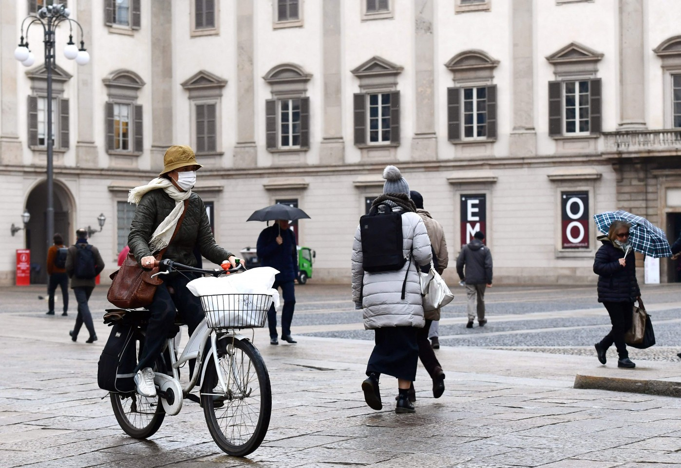 Difficulties in the mainland no longer stay within China as the Covid-19 epidemic sweeps the world. In this photo taken on 2 March 2020, a woman wearing a protective mask is seen crossing Piazza Duomo with her bicycle in Milan. (Miguel Medina/AFP)