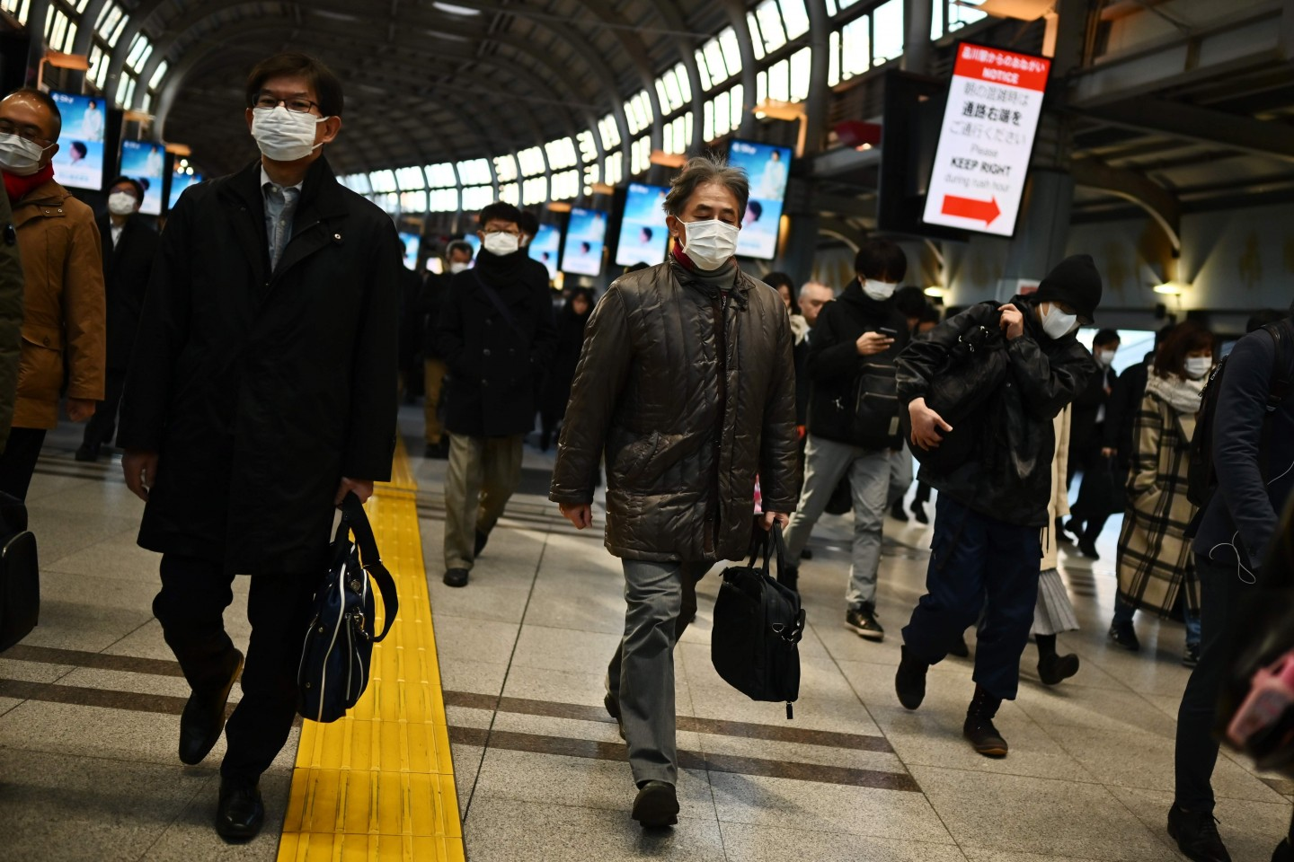 Mask-clad commuters make their way to work during the morning rush hour at the Shinagawa train station in Tokyo on 28 February 2020. (Charly Triballeau/AFP)