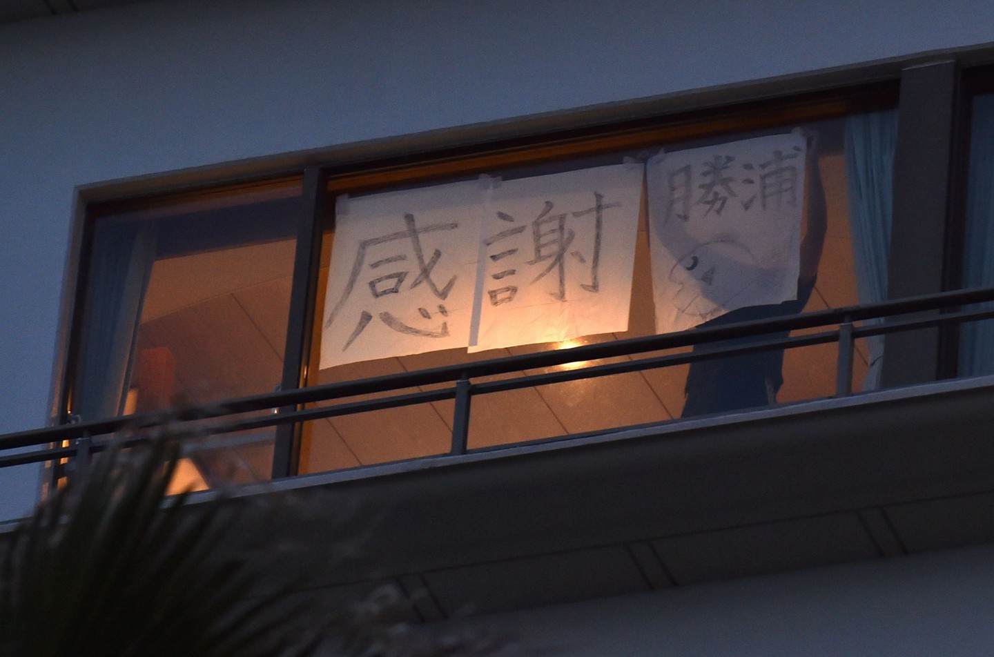 """A person who returned from Wuhan and is staying in quarantine in a hotel in Katsuura puts up the message """"Thank you, Katsuura"""" on the hotel window, on 12 February 2020. (Kazuhiro Nogi/AFP)"""
