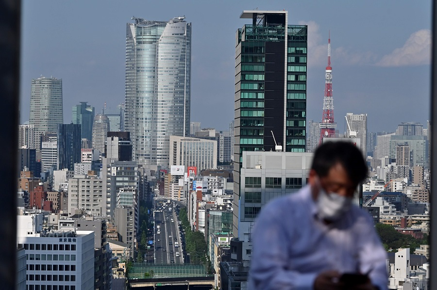 A man sitting on a rooftop looks at his phone before the city skyline in Tokyo on 8 June 2020. (Charly Triballeau/AFP)