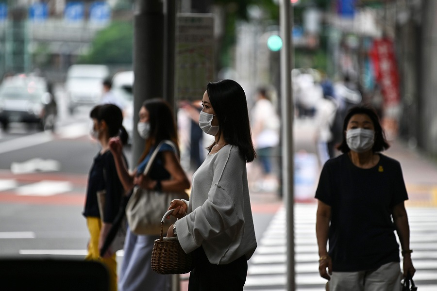 Face mask-clad pedestrians wait to cross a street in Tokyo on 24 July 2020. (Charly Triballeau/AFP)