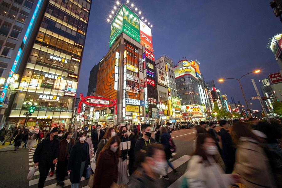 Pedestrians cross a street in Tokyo's Shinjuku area on 12 December 2020. (Kazuhiro Nogi/AFP)