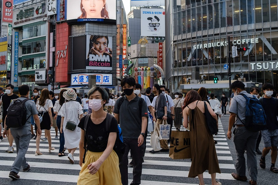 People walk on Shibuya crossing in Shibuya district of Tokyo, Japan, on 5 August 2021. (Yuki Iwamura/AFP)