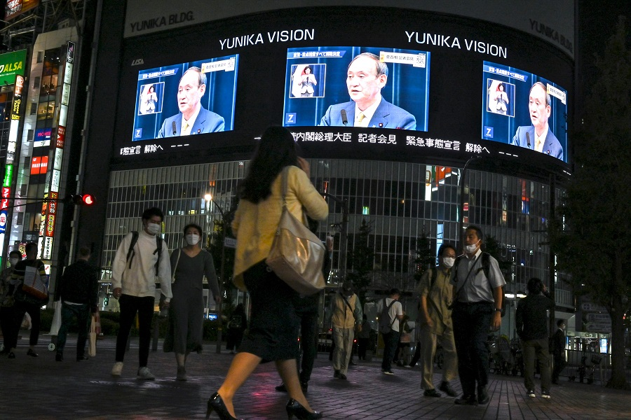 Pedestrians walk on a street and watch a live TV broadcast of Japan's Prime Minister Yoshihide Suga announcing the lift of the coronavirus state of emergency in Tokyo's Shinjuku area on 28 September 2021. (Kazuhiro Nogi/AFP)