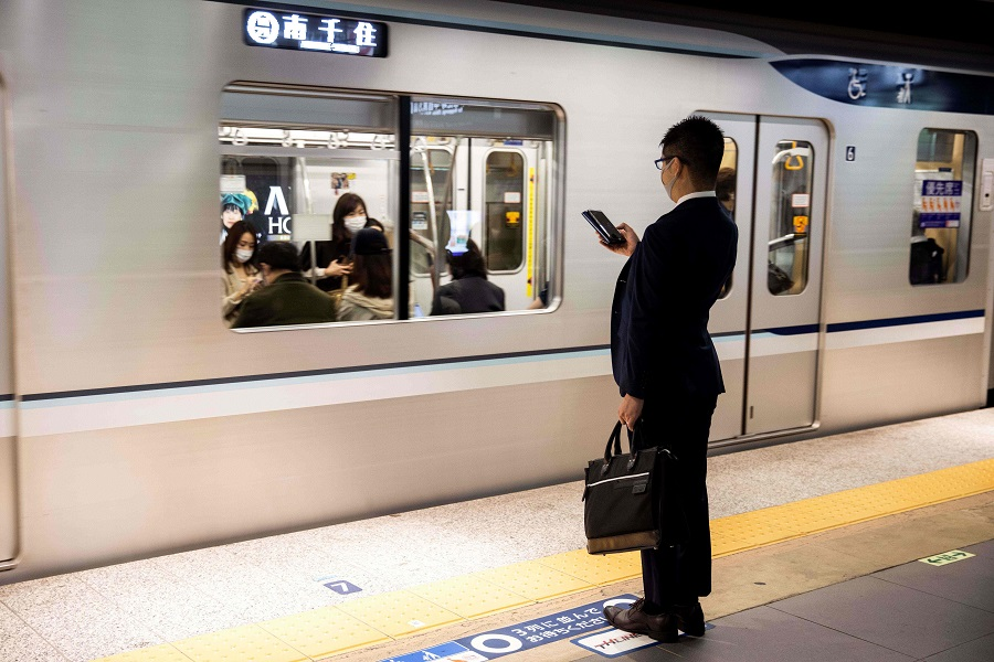 A commuter wearing a face mask checks his phone at Ginza Station in Tokyo on 19 November 2020. (Behrouz Mehri/AFP)