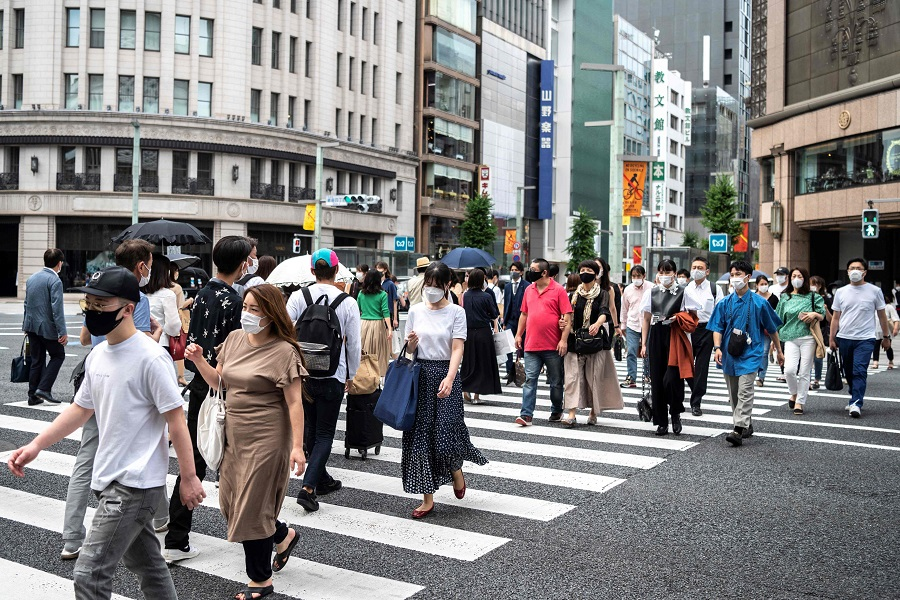 People cross a street in Tokyo's Ginza area, in Japan, on 22 June 2021. (Charly Triballeau/AFP)