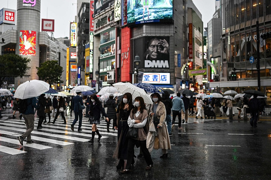 People use umbrellas to shelter from the rain while crossing a street in Tokyo on 19 October 2020. (Charly Triballeau/AFP)