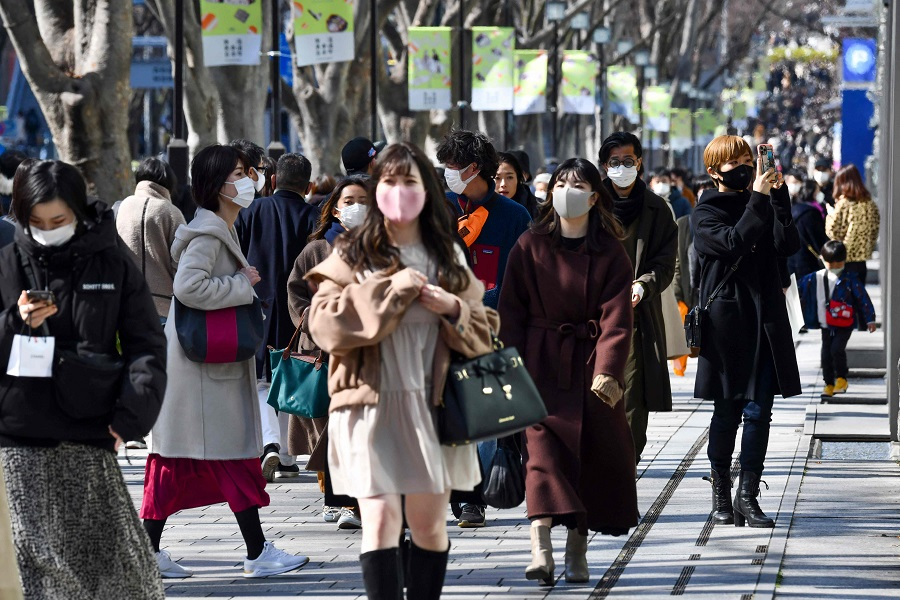 People wearing face masks walk along a street in the Harajuku shopping district in Tokyo on 27 February 2021. (Kazuhiro Nogi/AFP)