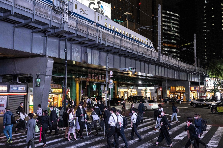 People cross a street while a Shinkansen leaves the city in Tokyo's Shimbashi area on 1 October 2021. (Charly Triballeau/AFP)