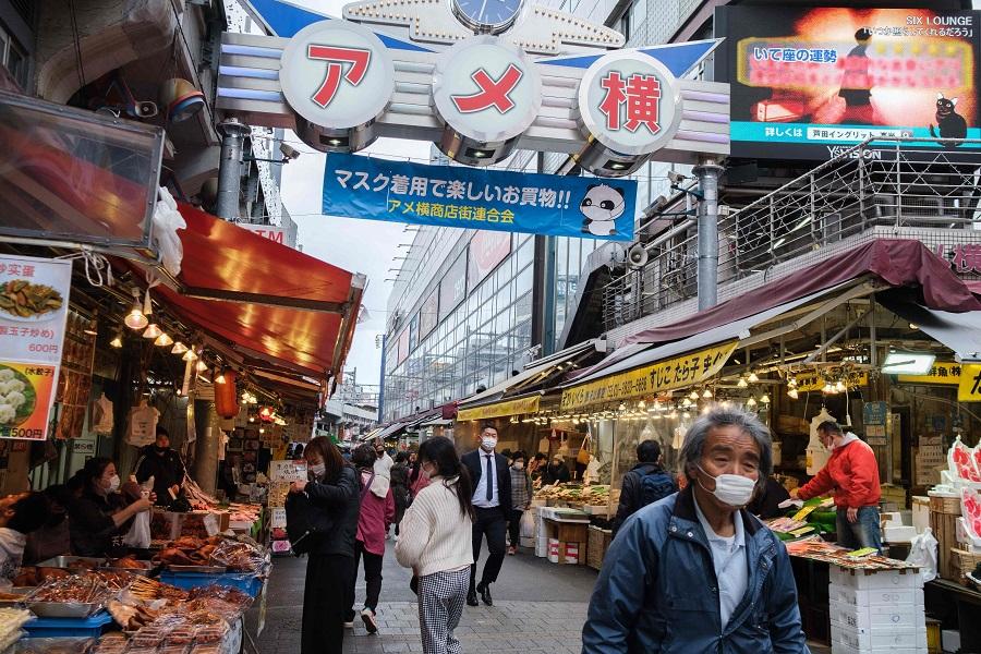 People walk through a street at the Ameyoko market in Ueno district of Tokyo, Japan, on 6 April 2021. (Yuki Iwamura/AFP)
