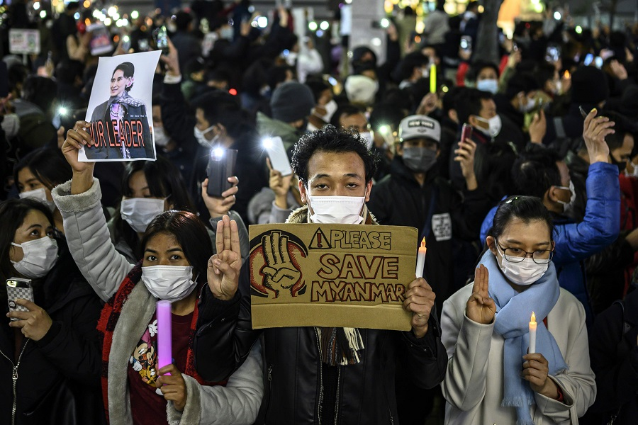 Myanmar activists hold up the three-finger salute and a picture of detained Myanmar civilian leader Aung San Suu Kyi during a protest in Tokyo on 6 February 2021, condemning the military coup in Myanmar. (Charly Triballeau/AFP)