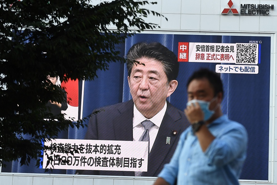 A man walks past a large screen showing Japanese Prime Minister Shinzo Abe's live press conference in Tokyo on 28 August 2020. (Philip Fong/AFP)
