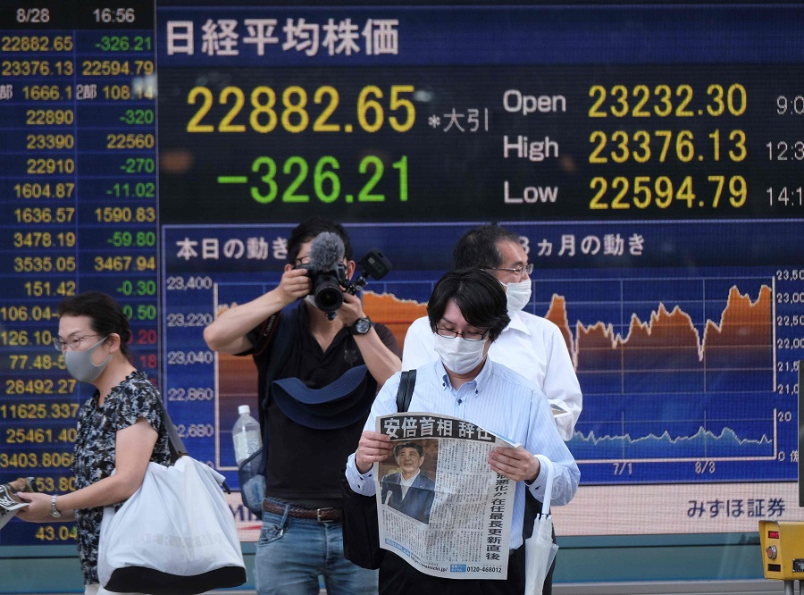 A pedestrin reads an extra edition of Japan Prime Minister Shinzo Abe's resignation in front of an electronic quotation board displaying share prices from the Tokyo Stock Exchange in Tokyo on 28 August 2020. (Kazuhiro Nogi/AFP)