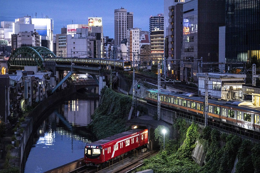 Trains travelling on three different rail lines are seen at dusk near Ochanomizu station in Tokyo, Japan, on 26 September 2021. (Charly Triballeau/AFP)