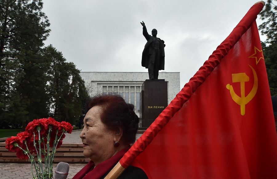 A woman holds a flag of the USSR during a gathering of Kyrgyz communist supporters to pay their respects to Soviet Union founder and revolutionary leader Vladimir Lenin during a rally marking the 151st anniversary of Lenin's birth, in central Bishkek, Kyrgyzstan, on 22 April 2021. (Vyacheslav Oseledko/AFP)