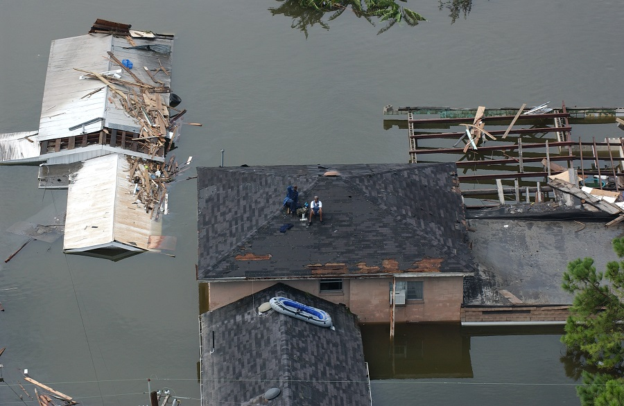 People sit on a roof waiting to be rescued after Hurricane Katrina, in New Orleans, Louisiana, US, 30 August 2005. (Jocelyn Augustino/FEMA; Wikimedia)
