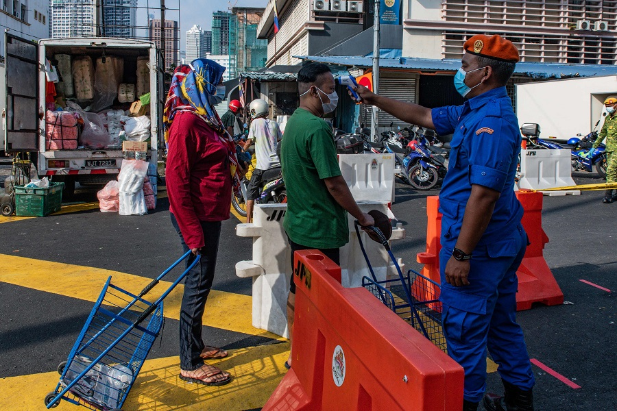 A member of the Malaysia Civil Defence Force checks the temperature of a man before entering the Chow Kit Market in Kuala Lumpur on 17 June 2020. (Mohd Rasfan/AFP)