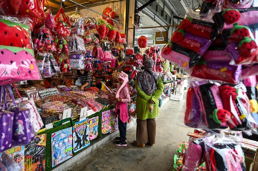 A girl buys souvenirs at the Kea Farm in Cameron Highlands near Brinchang in Malaysia's Pahang state on 28 November 2020. (Mohd Rasfan/AFP)