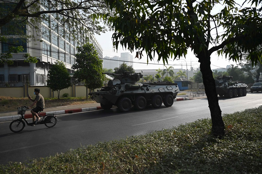 A man (left) he rides past military vehicles parked along a street in downtown Yangon on 15 February 2021, the morning after Myanmar's military cut the nation's internet and deployed extra troops around the country. (Ye Aung Thu/AFP)