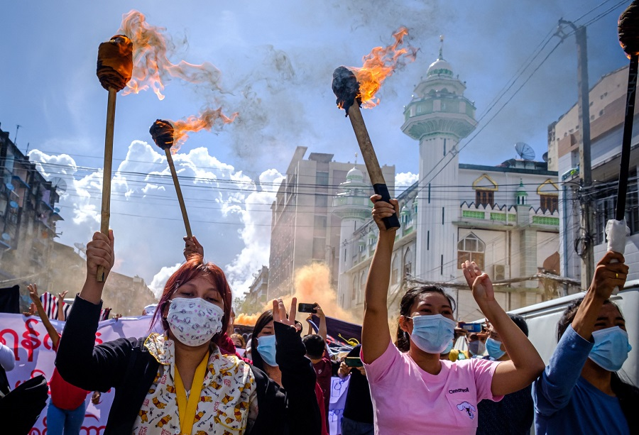 Women carry burning torches as they march during a demonstration against the military coup in Yangon, Myanmar, on 14 July 2021. (STR/AFP)