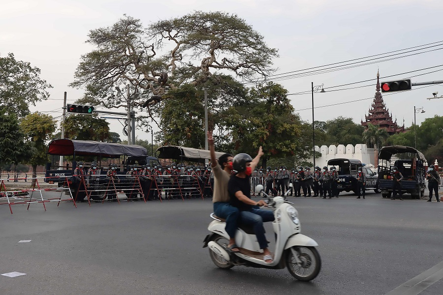 Protesters show the three finger salute to riot police as protesters hold a demonstration against the military coup near the royal palace in Mandalay, Myanmar, on 7 February 2021. (STR/AFP)