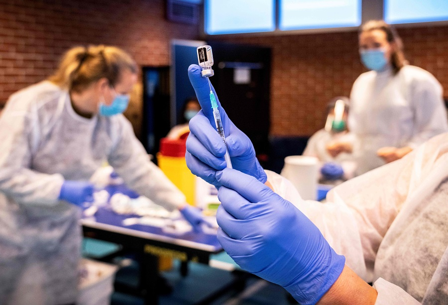 A nurse prepares a syringe with a vaccine against the Covid-19 coronavirus as residents who are over 85 years old and do not live in a nursing home are vaccinated, in Drammen, Norway, on 21 January 2021. (Ole Berg-Rusten/NTB/AFP)