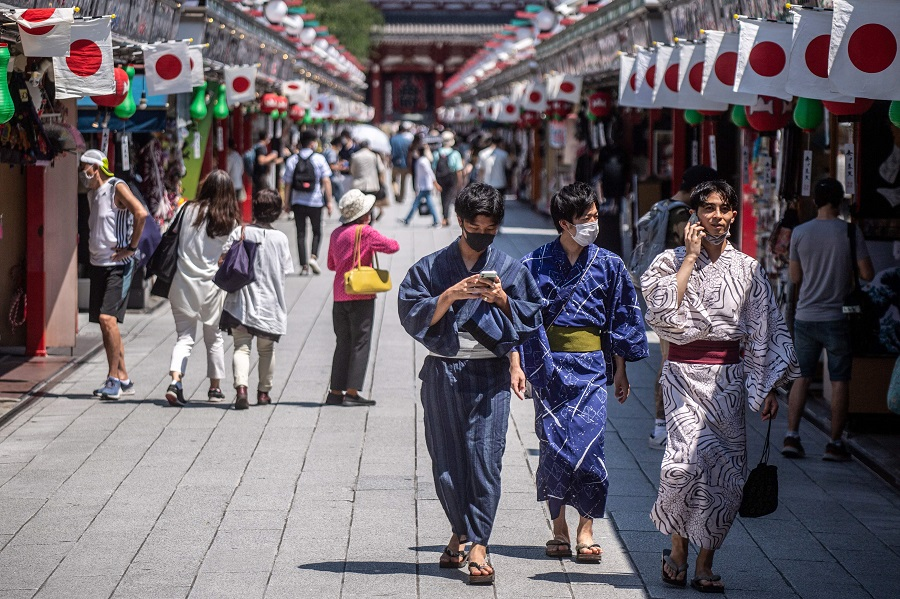 People in traditional outfits walk in Sensoji temple in Tokyo, Japan, on 22 July 2021. (Philip Fong/AFP)