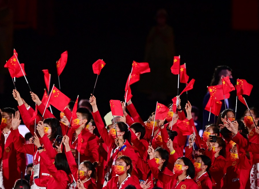 Members of China's delegation wave flags as they enter the Olympic Stadium during the opening ceremony of the Tokyo 2020 Olympic Games, in Tokyo, Japan, on 23 July 2021. (Franck Fife/AFP)