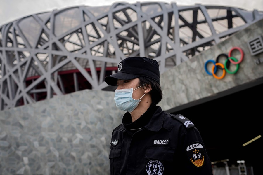 A security guard wearing a face mask amid the Covid-19 pandemic, stands guard at the site of the 2008 Beijing Olympics, in Beijing on 24 March 2020. (Nicolas Asfouri/AFP)