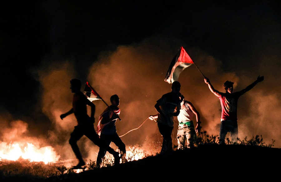 Palestinian protesters lift national flags as they burn tyres during a demonstration east of Gaza City by the border with Israel, on 15 June 2021, to protest the Israeli ultranationalist March of the Flags in Jerusalem's Old City which celebrates the anniversary of Israel's 1967 occupation of Jerusalem's eastern sector. (Mahmud Hams/AFP)