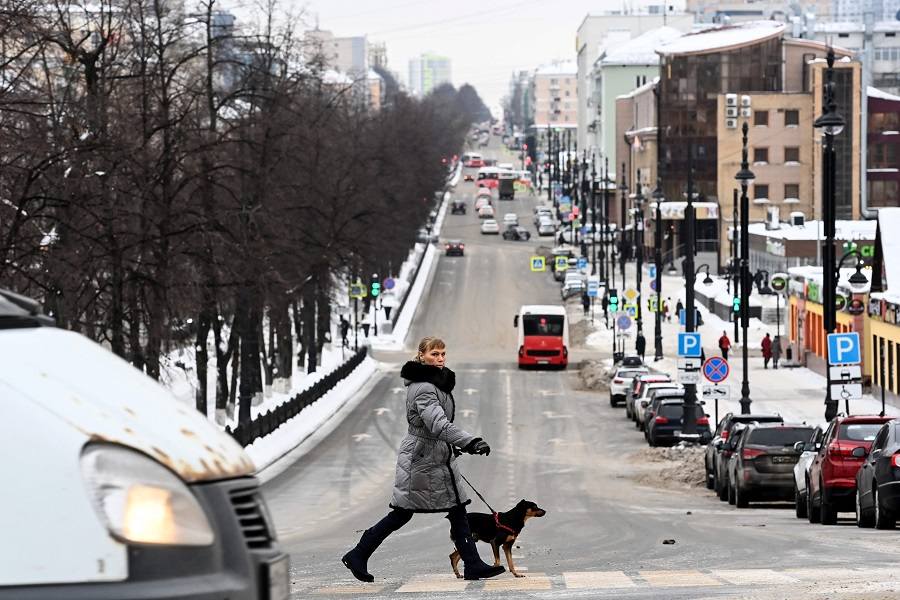 A woman with a dog crosses a street in Perm, Russia, on 27 January 2021. (Kirill Kudryavtsev/AFP)