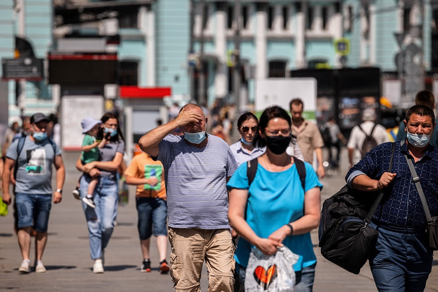 People wearing face masks walk down a street in Moscow, Russia, on 21 June 2021. (Dimitar Dilkoff/AFP)