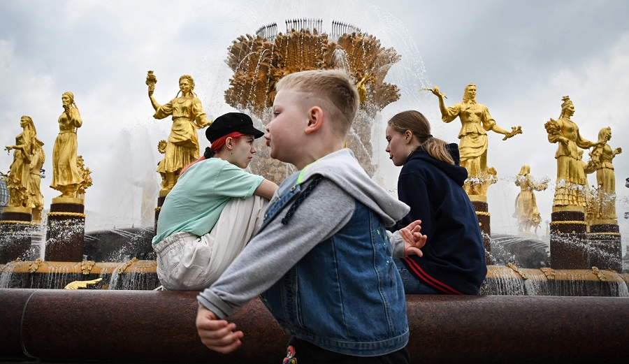 """Children sit at the """"Friendship of Nations"""" fountain, built in 1954, symbolising the friendship of sixteen Soviet republics forming the USSR, at the All-Russia Exhibition Centre (VDNKh) in Moscow, Russia, on 27 May 2021. (Alexander Nemenov/AFP)"""