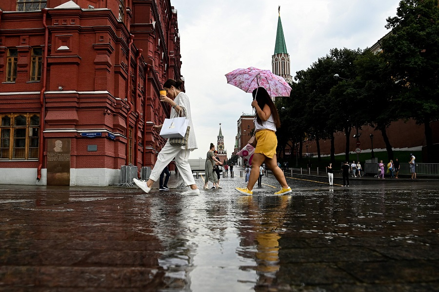 People walk through a puddle after the rain in downtown Moscow, Russia, on 10 August 2021. (Kirill Kudryavtsev/AFP)