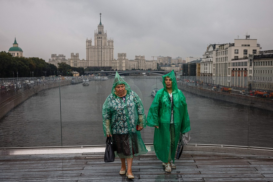 Women wearing plastic rain coats walk on a pedestrian bridge near a Stalin-era skyscraper on Kotelnicheskaya embankment on the northern bank of the Moskva River in Moscow, Russia, on 11 August 2021. (Dimitar Dilkoff/AFP)