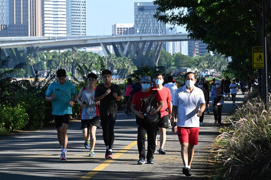 People walk and jog along the park connector at Marina Bay East as they enjoy the holiday to mark the country's National Day holiday in Singapore on 9 August 2021. (Roslan Rahman/AFP)