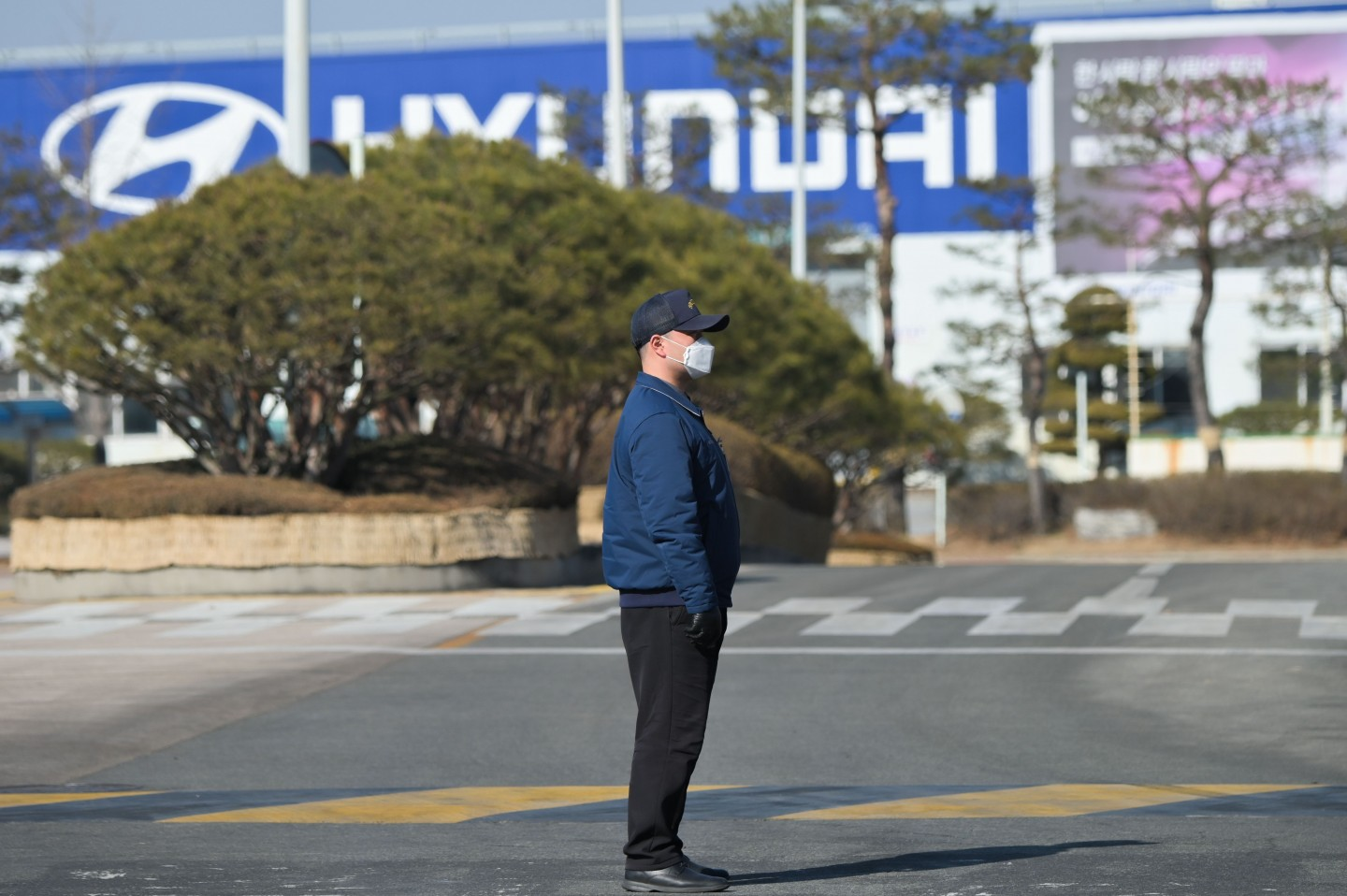 In a photo taken on 10 February 2020 a security guard stands at the entrance to the Hyundai Motor Asan Factory in Asan, south of Seoul. Hyundai has had to suspend production at its factories across South Korea, putting 25,000 workers on forced leave and partial wages, hamstrung by a lack of parts with the coronavirus outbreak crippling China's industrial output. (Yelim Lee/AFP)