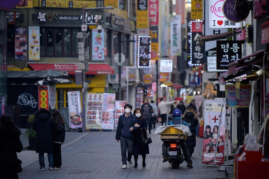 Shoppers walk along a street in the Myeongdong district of Seoul on 28 December 2020. (Ed Jones/AFP)