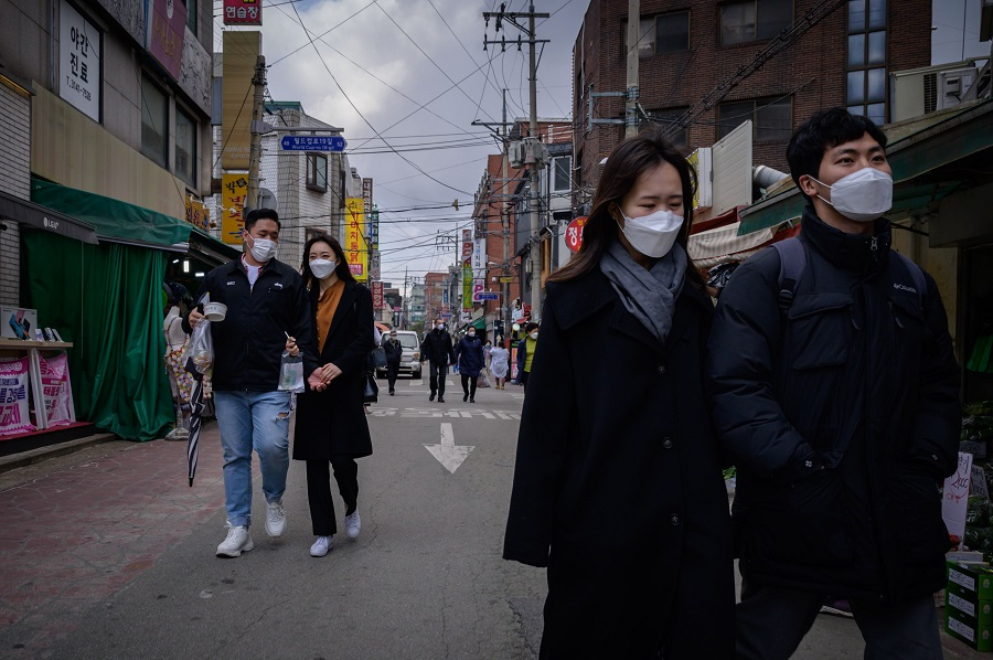 People wearing face masks amid concerns over the Covid-19 coronavirus walk through a market in Seoul on 22 April 2020. (Ed Jones/AFP)