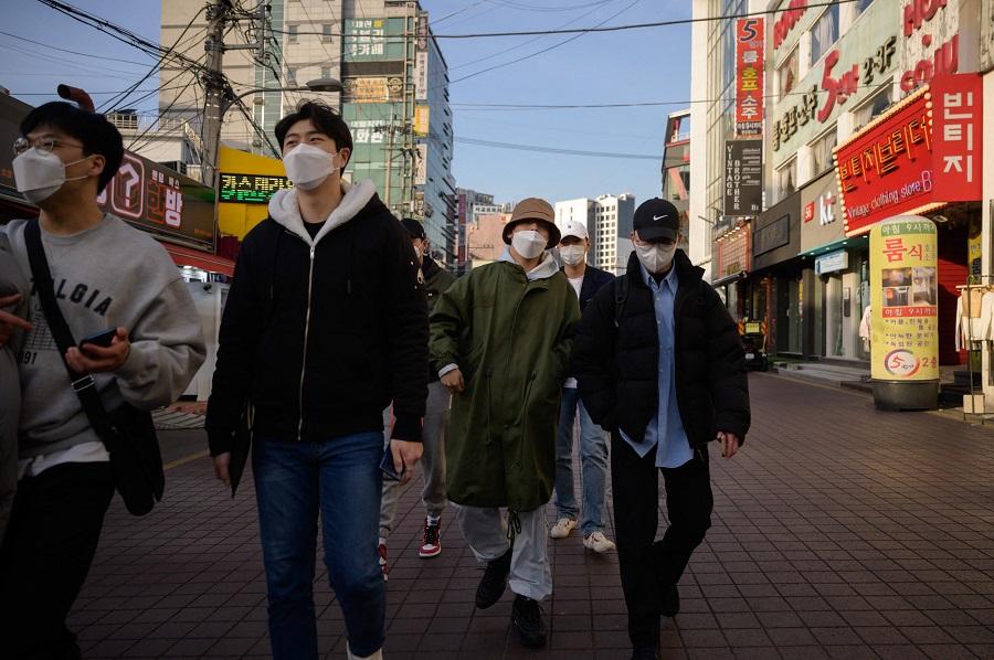 People walk along a street in Seoul, Korea, on 24 February 2021. (Ed Jones/AFP)