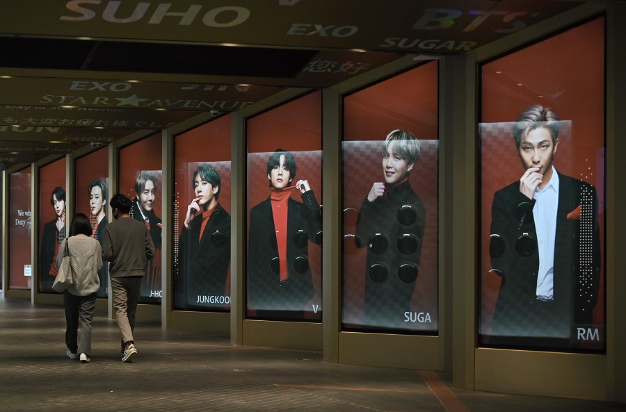 People walk past commercial posters showing K-pop group BTS members outside a duty free shop in Seoul on 6 October 2020. (Jung Yeon-je/AFP)