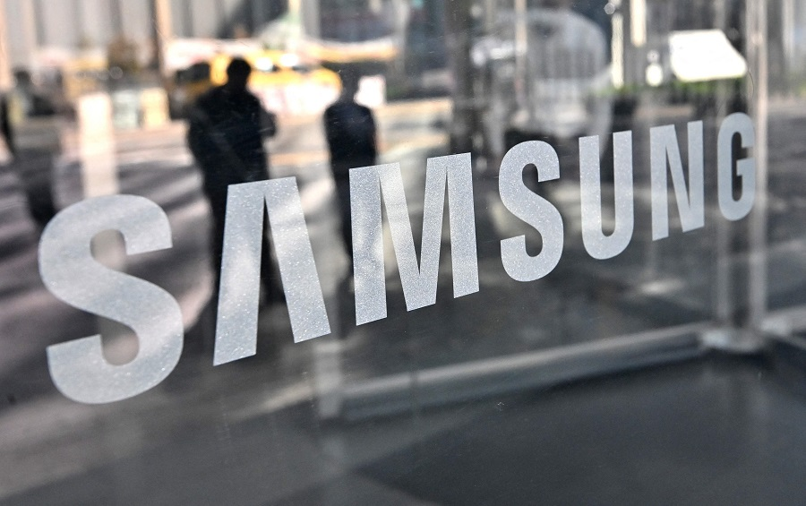 In this file photo taken on 6 April 2021, people walk past the logo of Samsung Electronics at the company's Seocho building in Seoul, South Korea. (Jung Yeon-je/AFP)