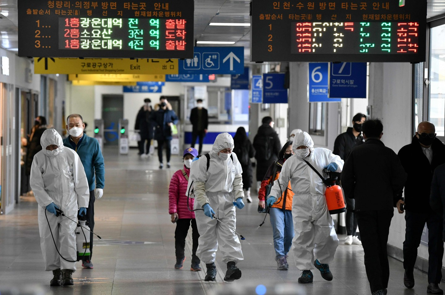Workers wearing protective gear spray disinfectant to help prevent the spread of the Covid-19 coronavirus, at a subway station in Seoul on 13 March 2020. (Jung Yeon-je/AFP)