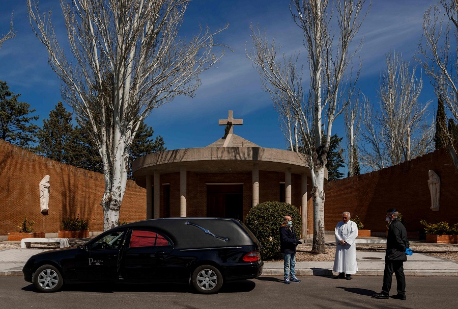 Mortuary employees wearing face masks stand next to a priest before the burial of a Covid-19 coronavirus victim at the Fuencarral cemetery in Madrid on 29 March 2020. (Baldesca Samper/AFP)